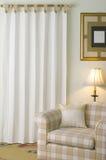 Fåtölj och gardin i tillfälligt vardagsrum Arkivbild