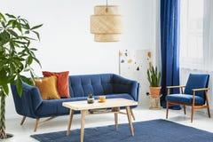 Fåtölj och soffa i blå och orange vardagsruminre med lampan ovanför trätabellen Verkligt foto royaltyfria bilder