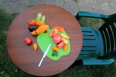 Fåtölj och tabell med skivade tomater och peppar i trädgårdPA Royaltyfria Bilder