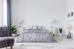 Fåtölj och växter i den vita eleganta sovruminre med säng mellan kabinetter med lampor Verkligt foto arkivbilder