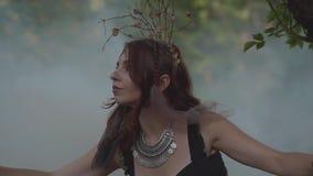 Fée attirante de dryade ou de forêt avec des Afro-tresses et des tatouages sur la danse de corps dans le beau costume dans le nua banque de vidéos