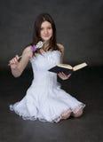 Fée dans une robe blanche avec la baguette magique et le livre magiques Images libres de droits