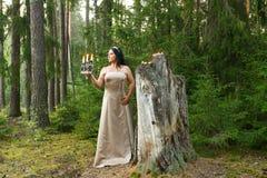Fée de forêt dans une robe légère à un grand tronçon avec un chandelier avec des bougies plan global photos libres de droits
