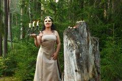 Fée de forêt dans une robe légère avec un masque sur son visage dans la forêt avec un chandelier avec des bougies photo stock