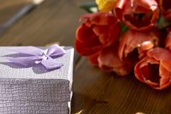 Félicitations les vacances avec un cadeau et des fleurs fraîches Photos libres de droits