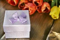 Félicitations les vacances avec un cadeau et des fleurs fraîches Photos stock