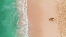 Férias da praia na ilha tropical do paraíso, na mulher 'sexy' do bronzeado que relaxam no fundo idílico do verão na água clara e  filme