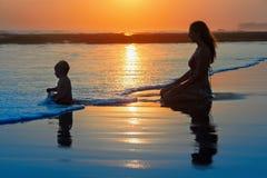 Férias de família Mãe com a criança na praia do por do sol imagem de stock