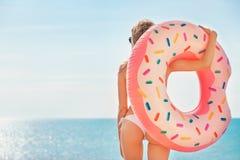 Férias de verão Apreciando a mulher do bronzeado no biquini branco com o colchão da filhós perto da piscina foto de stock royalty free