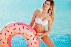 Férias de verão Apreciando a mulher do bronzeado no biquini branco com o colchão da filhós perto da piscina imagem de stock