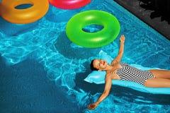 Férias de verão Banho de sol da mulher, flutuando na água da piscina Imagem de Stock