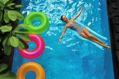 Férias de verão Banho de sol da mulher, flutuando na água da piscina Imagem de Stock Royalty Free