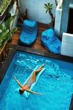 Férias de verão Banho de sol da mulher, flutuando na água da piscina Imagens de Stock