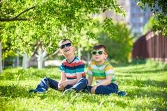 Férias de verão felizes Duas crianças felizes em um gramado verde em um s Imagens de Stock Royalty Free