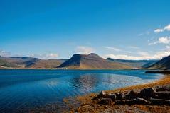 Férias de verão no isafjordur, Islândia Litoral montanhoso no céu azul ensolarado Paisagem da montanha vista do mar descubra imagens de stock
