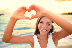 Férias do amor - mulher que mostra o coração na praia Foto de Stock Royalty Free