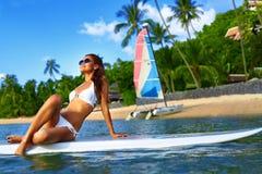 Férias do curso Mulher a bordo no mar Menino e meninas que sentam-se na mesa surfando e no olhar no mar azul esportes foto de stock royalty free