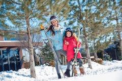 Férias do inverno Da família do tempo mulher e menina junto fora nos óculos de proteção com os esquis que levantam mostrando o th imagens de stock