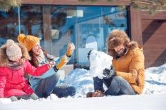 Férias do inverno Tempo da família junto que senta fora o jogo com o riso da neve alegre fotografia de stock