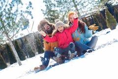 Férias do inverno Tempo da família junto que senta fora o riso de jogo da neve alegre imagens de stock royalty free