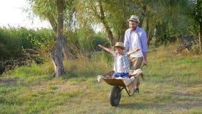 Férias em família alegres na natureza, o paizinho leva o menino alegre da criança em um carrinho de mão no movimento lento video estoque