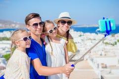 Férias em família em Europa Pais e crianças que tomam a cidade de Mykonos do fundo da foto do selfie em Grécia Foto de Stock Royalty Free