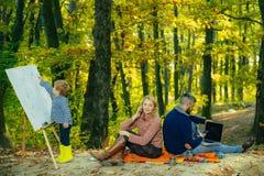 Férias em família felizes no parque do outono O menino bonito tira a imagem na natureza Conceito de família feliz outono que acam imagem de stock royalty free