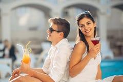 Férias loving da despesa dos pares na piscina tropical do recurso Lua de mel dos recém-casados no beira-mar foto de stock