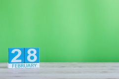 28 février Cubez le calendrier pour le 28 février sur le bureau en bois avec le fond vert et l'espace vide pour le texte Pas saut Image libre de droits