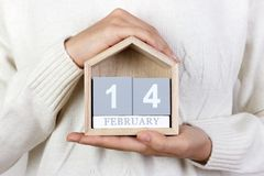 14 février dans le calendrier la fille tient un calendrier en bois Saint-Valentin, le jour international du cadeau des livres, jo Photos libres de droits