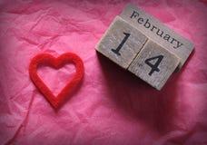 14 février et coeur de coupe de rouge sur le papier rose Photos libres de droits