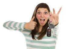 Fêmea étnica com chaves do carro e polegares acima no branco Foto de Stock