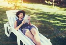Fêmea adolescente brasileira no daybed com a tabuleta digital no jardim fotos de stock