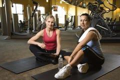 Fêmea adulta com o instrutor pessoal na ginástica. Fotos de Stock