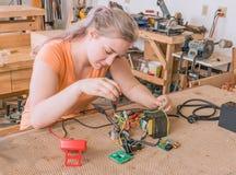 Fêmea adulta nova que trabalha em componentes de circuito de montagem imagens de stock