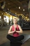 Fêmea adulta que senta-se na posição da ioga sobre a esteira. fotografia de stock royalty free