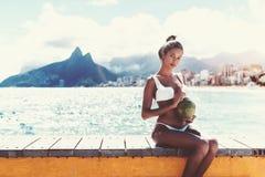Fêmea afro-americana no banco da praia com coco imagens de stock
