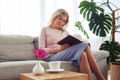 Fêmea agradável da idade 40-50 que concentram-se no livro de leitura Foto de Stock Royalty Free
