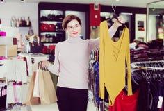 A fêmea 2-30 anos velha está mostrando-lhe compras Imagens de Stock Royalty Free