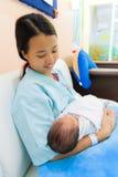 Fêmea asiática com o recém-nascido nos braços Fotografia de Stock