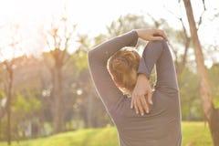 Fêmea asiática no exercício cinzento do sportswear no parque imagens de stock