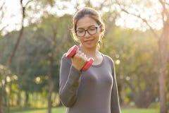 A fêmea asiática no sportswear cinzento está levantando o peso imagens de stock royalty free