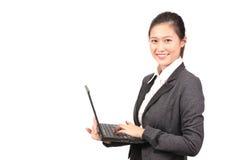 Fêmea asiática no vestuário do negócio que guarda um portátil Foto de Stock