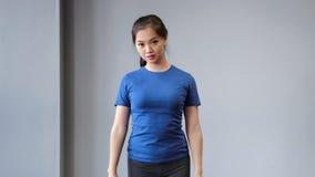 Fêmea asiática nova segura da aptidão que faz o exercício do exercício usando os pesos que apreciam o treinamento vídeos de arquivo