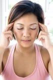 Fêmea asiática que aplica a pressão delicada no templo Foto de Stock