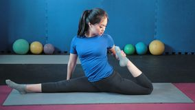 Fêmea asiática segura flexível que senta-se na guita que faz esticando o tiro completo vídeos de arquivo