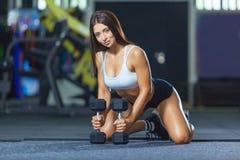 A fêmea atlética senta-se em um assoalho no sportswear em um clube do gym perto dos pesos imagem de stock royalty free