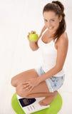 Fêmea atrativa nova que squatting no sorriso da escala Imagem de Stock Royalty Free