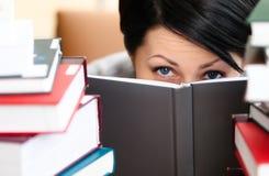 A fêmea atrativa olha para fora sobre o livro Imagens de Stock Royalty Free