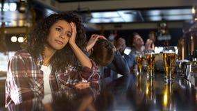 Fêmea biracial desapontado com os amigos masculinos que olham o jogo na barra, perda do esporte imagem de stock